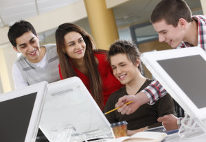 four young students study on computers in a college campus